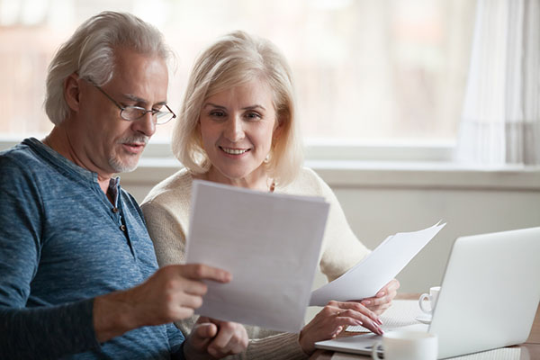 Happy older couple saving money for retirement and looking over their retirement plans
